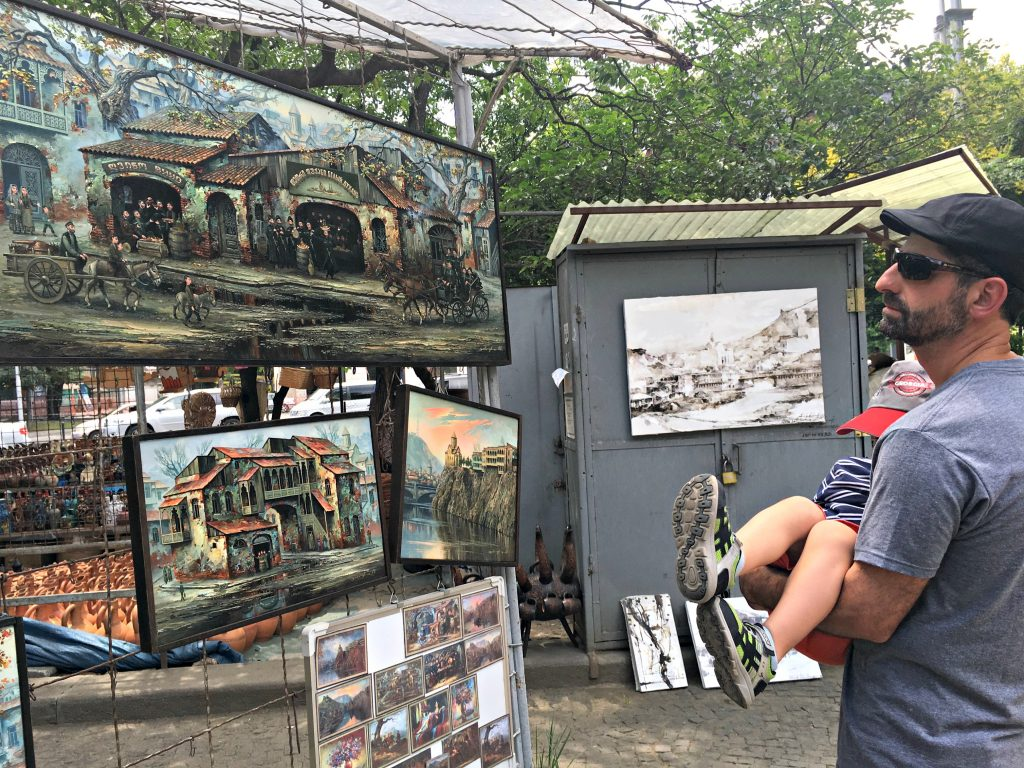 Man looking at displayed paintings at the Dry Bridge