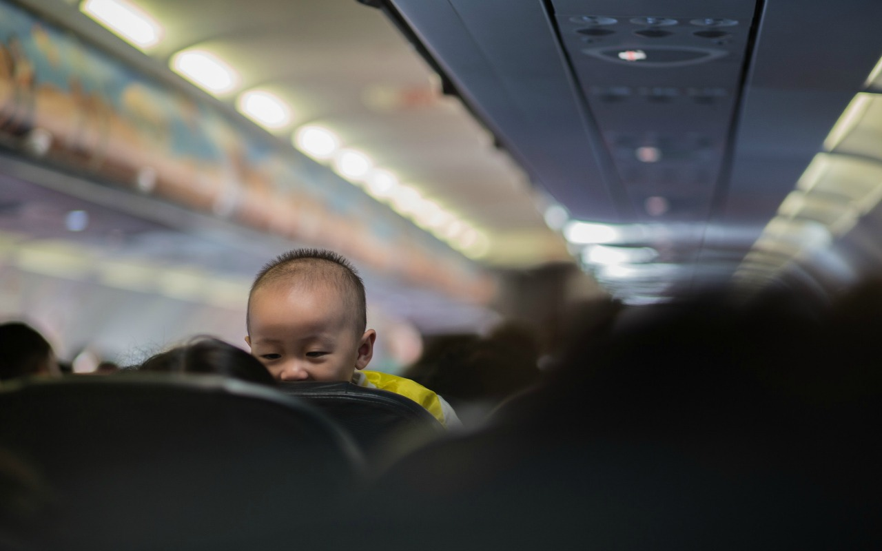 Child looking back over the seat on an airplane