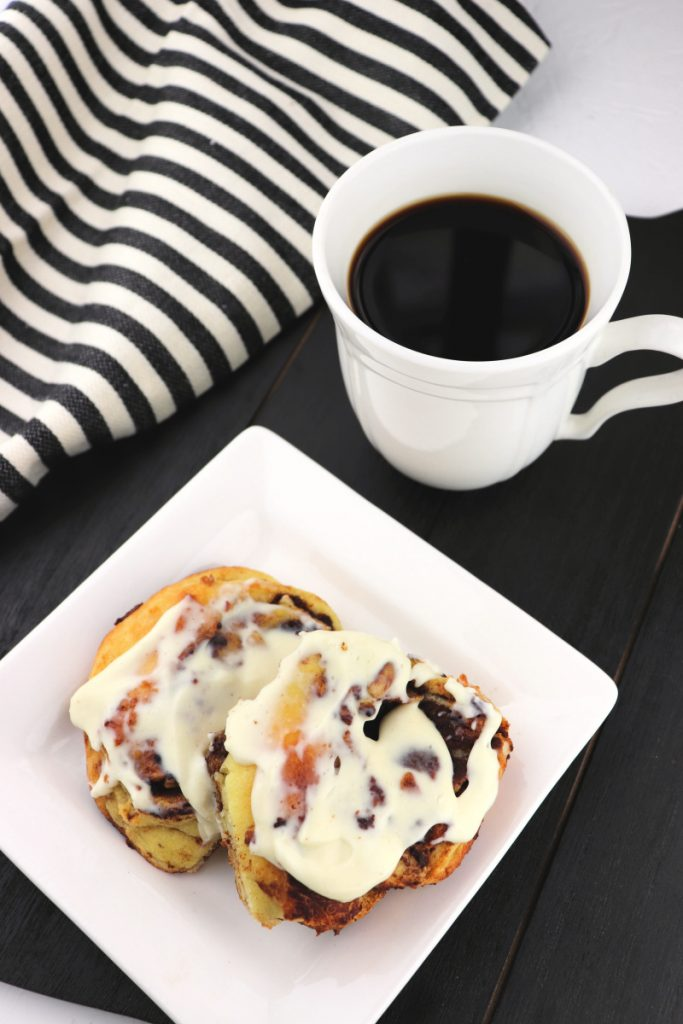 Two keto cinnamon rolls on a white plate next to a mug of coffee