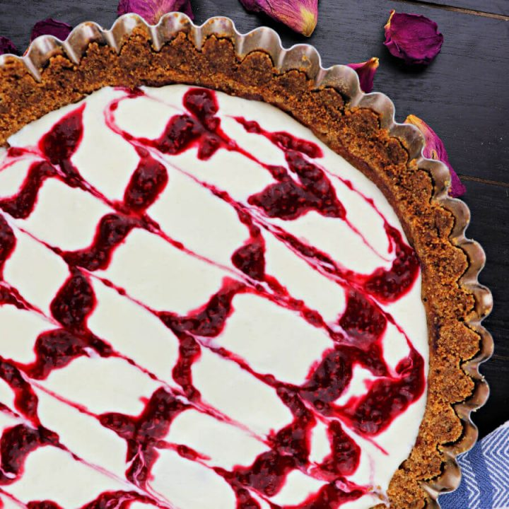 Keto bakewell tart is the perfect summer dessert! The flavors of fresh raspberries and almonds in a creamy tart with almond flour shell. #ketodessert #lowcarbdessert