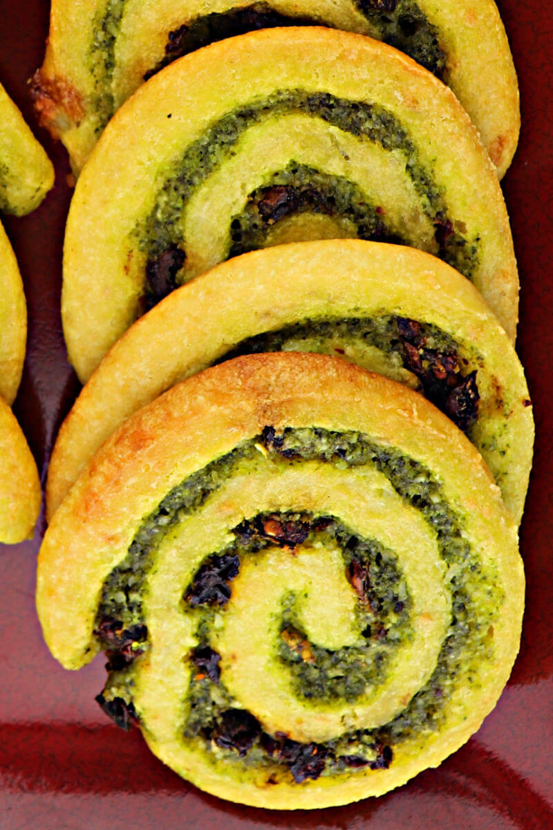 Delicious parmesan, basil, garlic, and sun-dried tomatoes flavor these keto pesto pinwheels. Perfect for a low carb appetizer or gluten-free game day snack. #ketoappetizer #glutenfreeappetizer