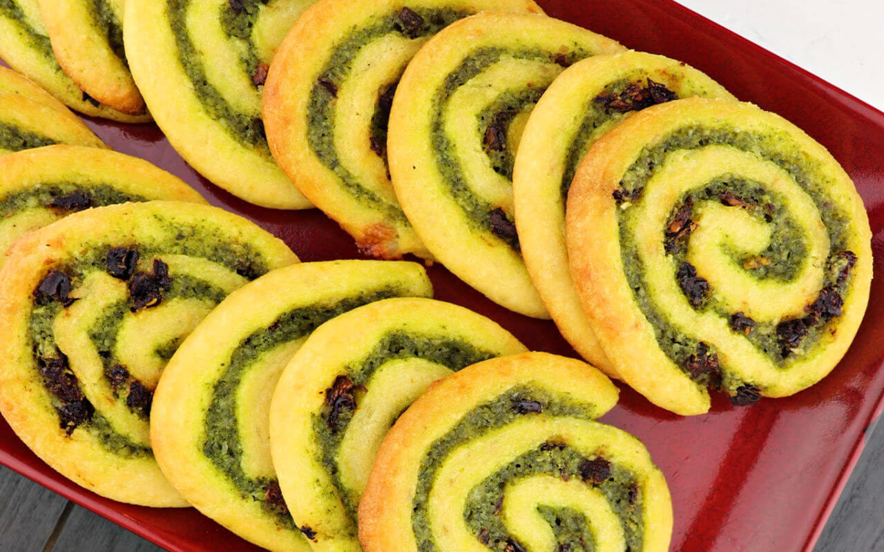 Plate of flavorful keto pesto pinwheels. Garlic, basil, and sundried tomato flavors in a fabulous appetizer. #ketoappetizer #glutenfreepinwheels