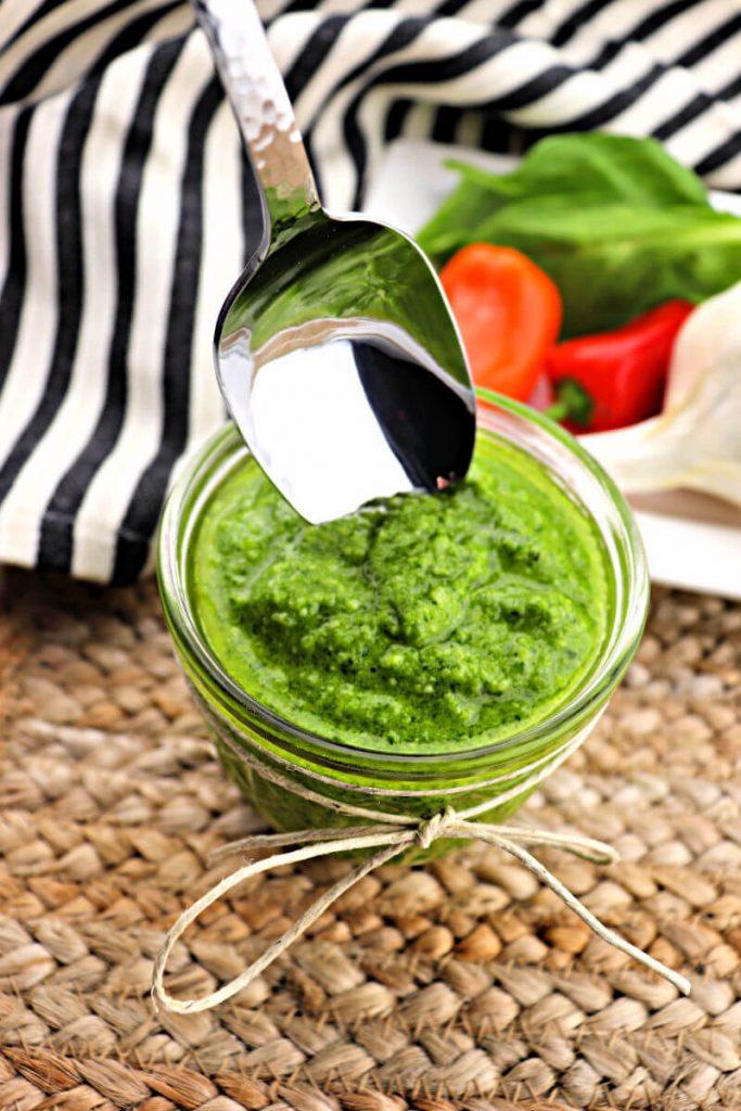 Spoon dips into a jar of basil keto pesto sauce. #ketorecipes #italianketo