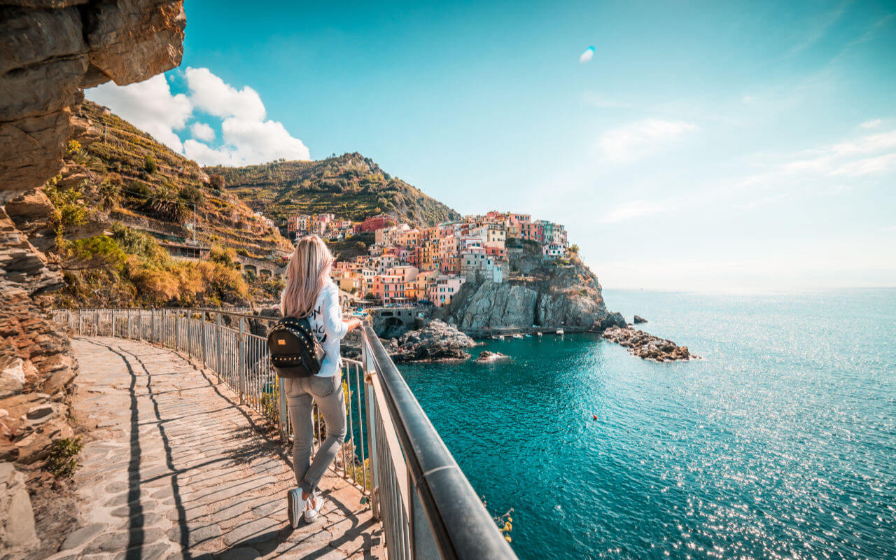 Middle grade books to inspire wanderlust, traveler admires manarola town, Italy #middlegradebooks #yabooks #familytravel