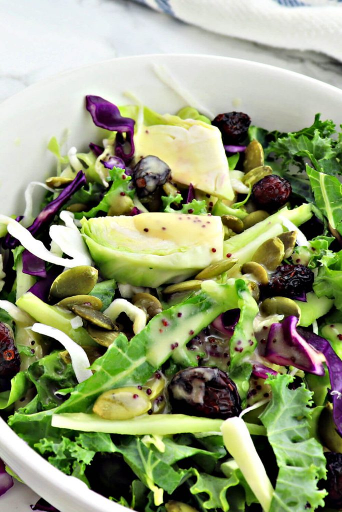 Kale crunch salad with lemon poppyseed keto salad dressing is sugar-free yet sweet and crunchy. The perfect low carb option for a holiday dinner or get-together with pumpkin seeds and cranberries. #ketoyum #kalesalad #lowcarbsides