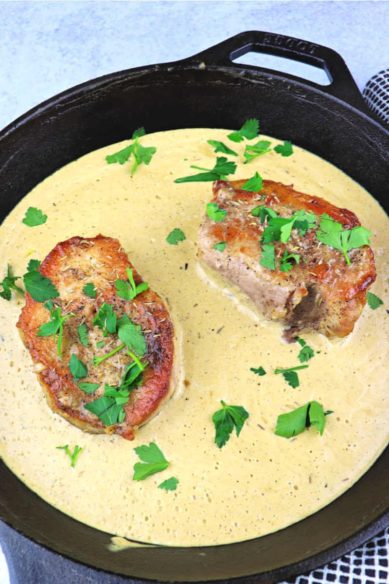 Creamy garlic keto pork chops are family dinner comfort food. Smothered or gluten-free gravy on the side, keto dinner served. #ketoporkchops #ketodinner