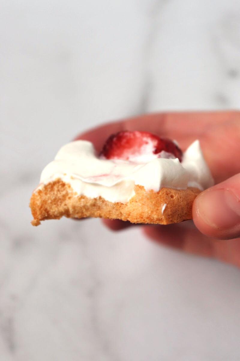 Bite out of a strawberry keto meringue cookie. #ketomeringuecookies #ketodesserts #ketorecipes
