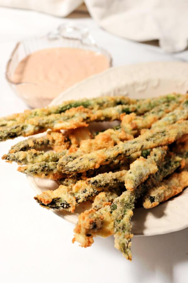 Baked keto asparagus fries served with spicy sugar-free lemon garlic dip.