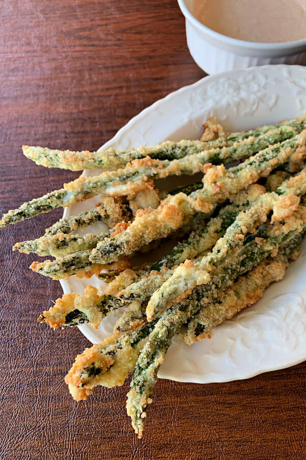 Crispy keto baked asparagus fries coated with parmesan and pork rind powder. Served with a flavorful spicy lemon garlic dip.