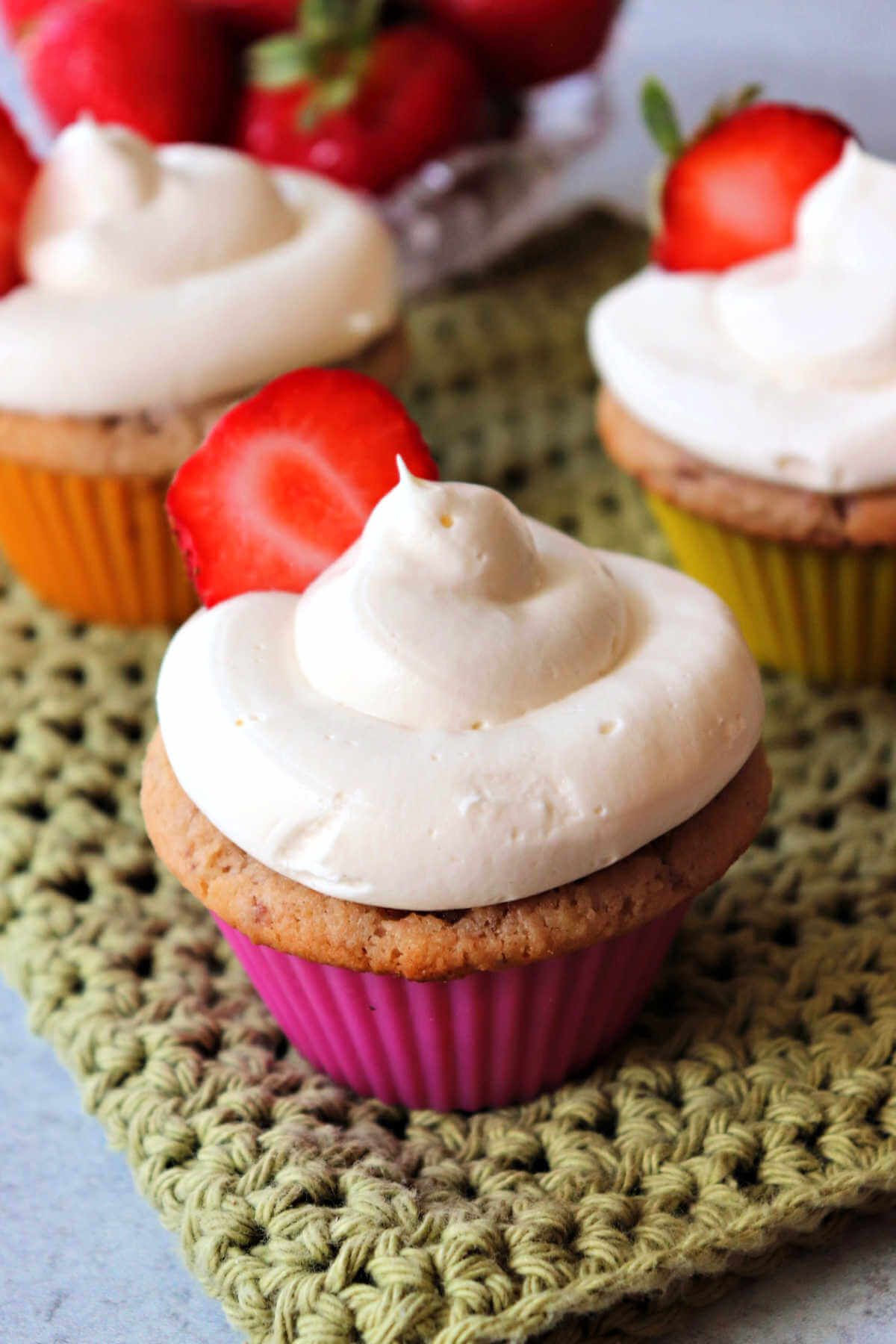 Keto strawberry cupcakes topped with sugar-free cream cheese frosting.