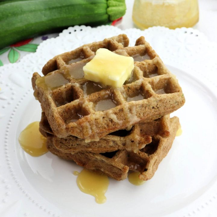 A stack of three keto zucchini waffles on a white plate.