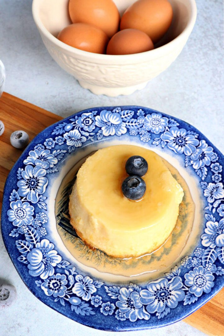 Keto flan on a blue plate with eggs in background