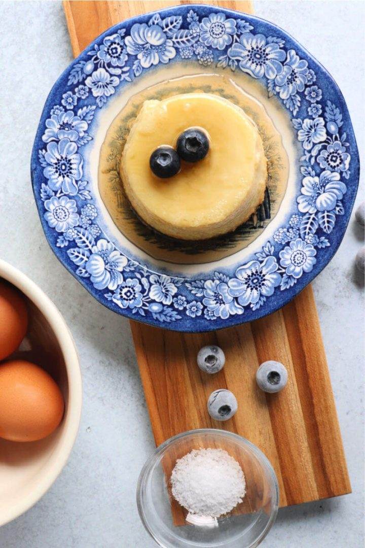Overhead a serving of keto flan on a board with ingredients