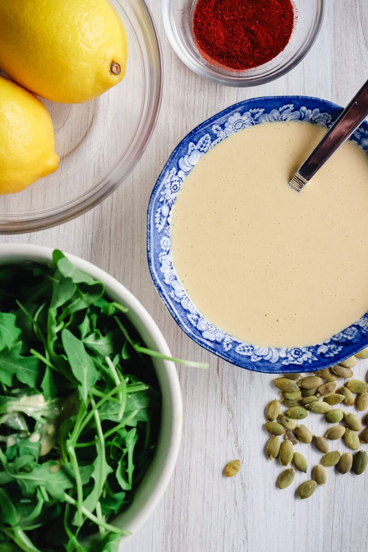 Keto Tahini dressing in a bowl with ingredients around