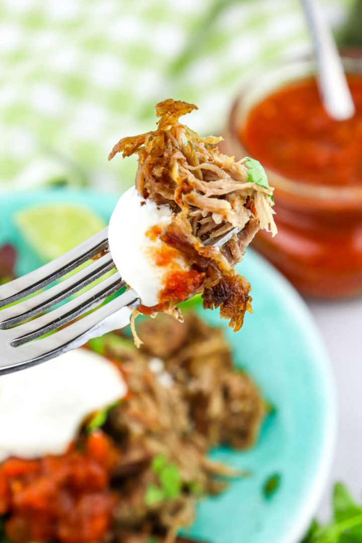 Bite of keto carnitas with sour cream