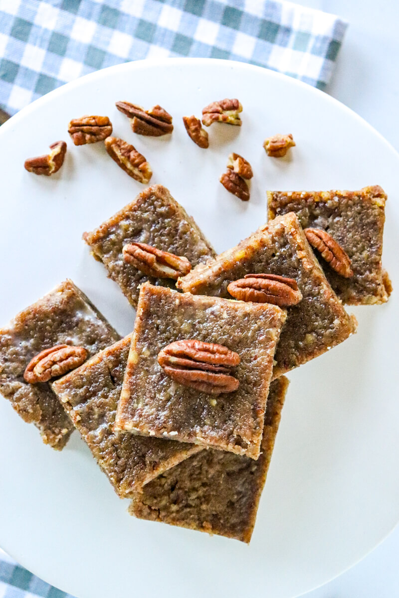 Keto pecan pie bars stacked on a white plate