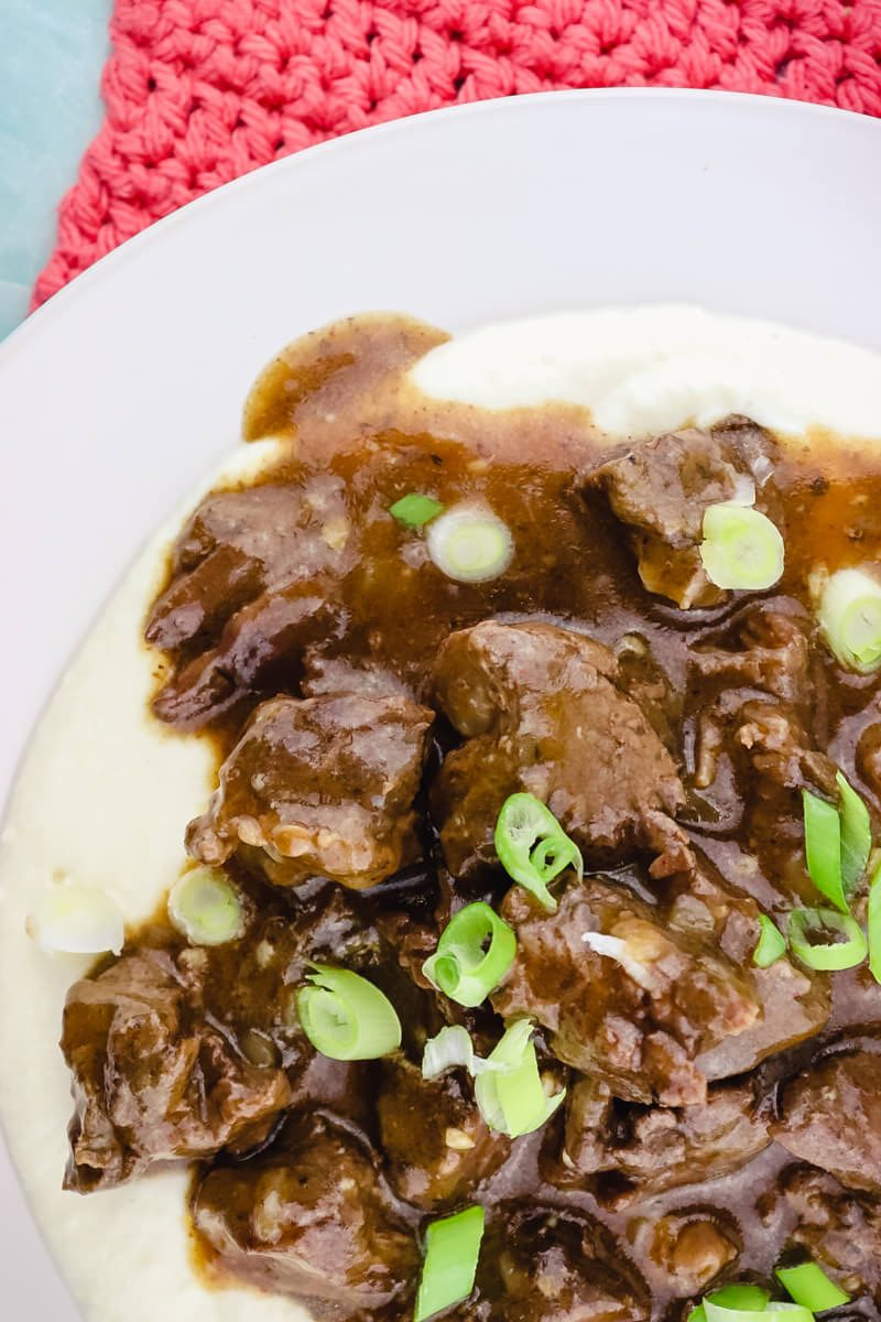 Easy keto beef tips with gravy on a plate with cauliflower mashed potatoes