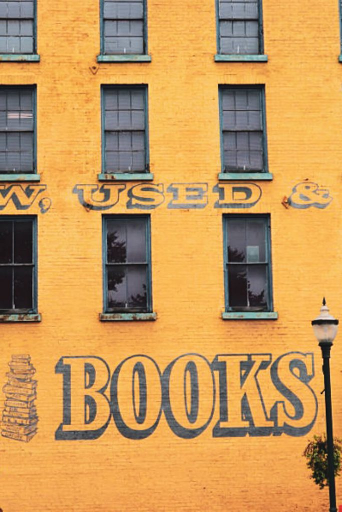 """Outside view of yellow building on which is written """"books"""""""