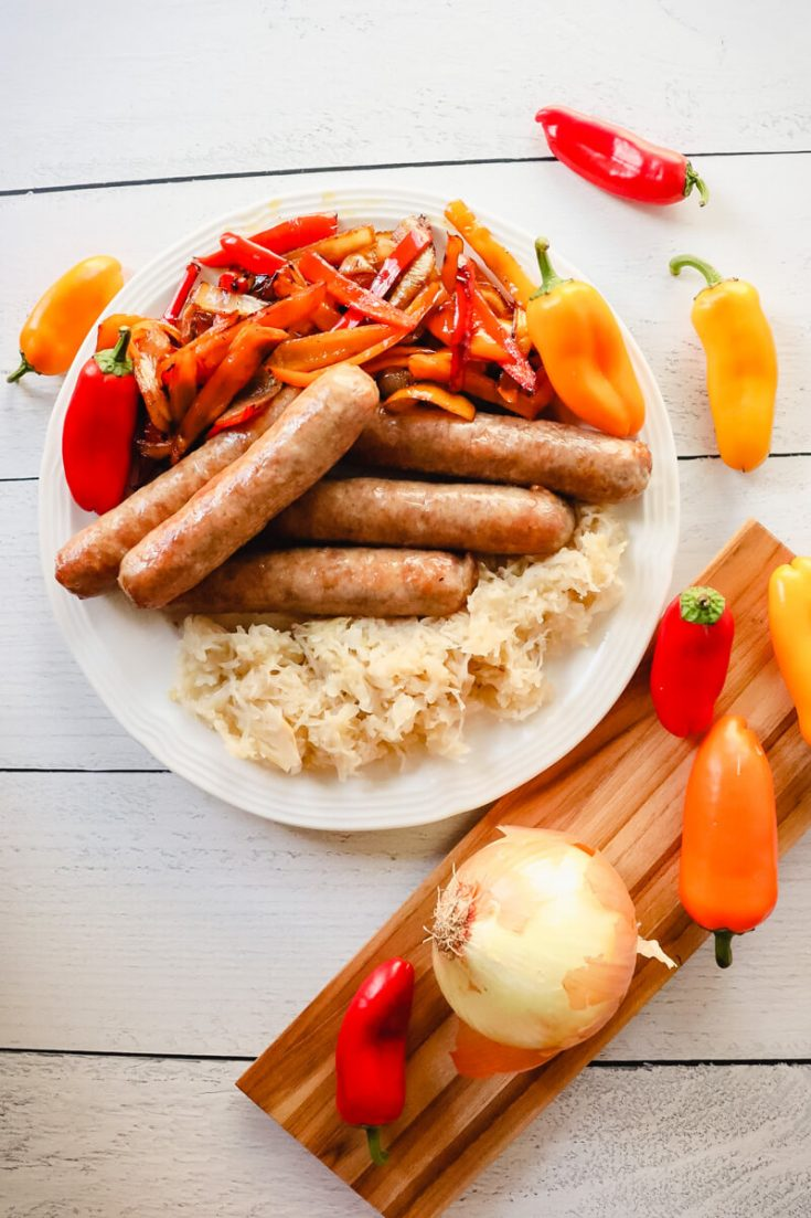 Overhead view of brats with peppers and onions
