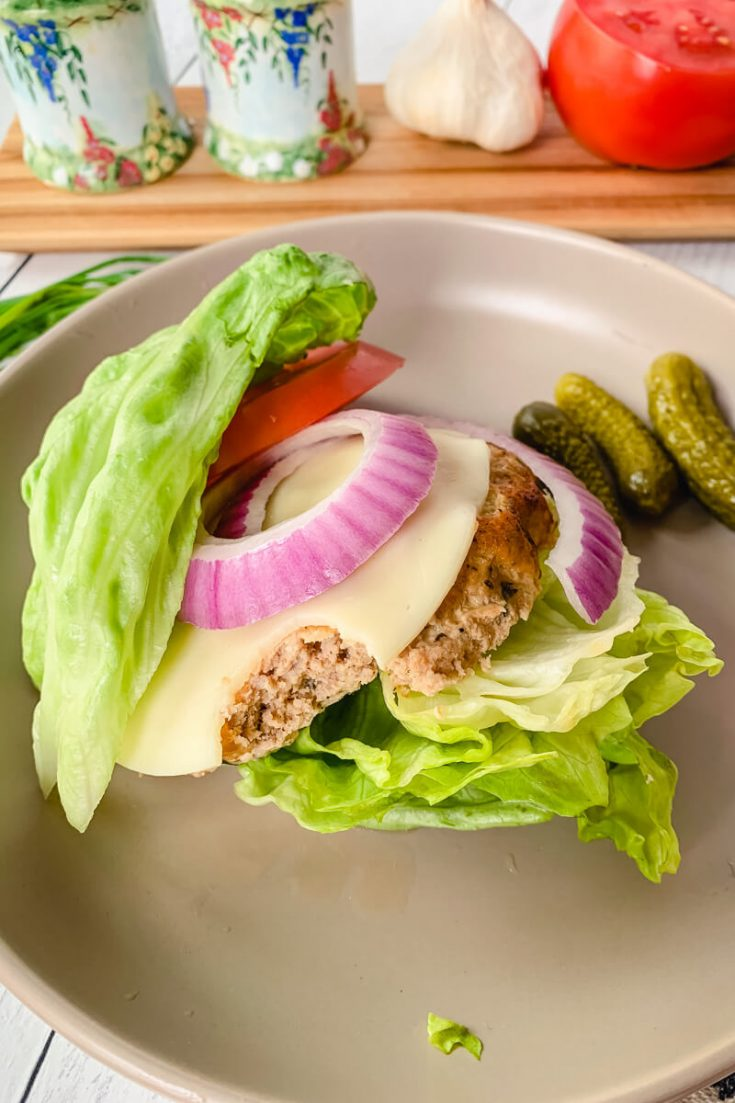 Bite out of a keto turkey burger on a plate
