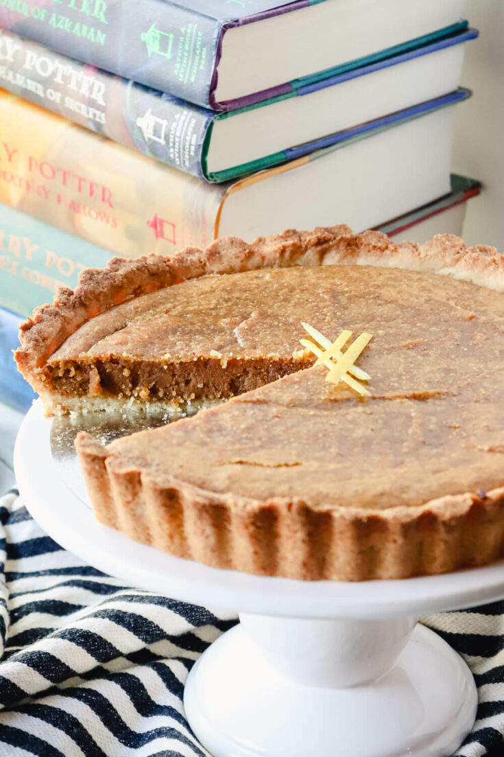 Piece cut out of the keto treacle tart with books in background