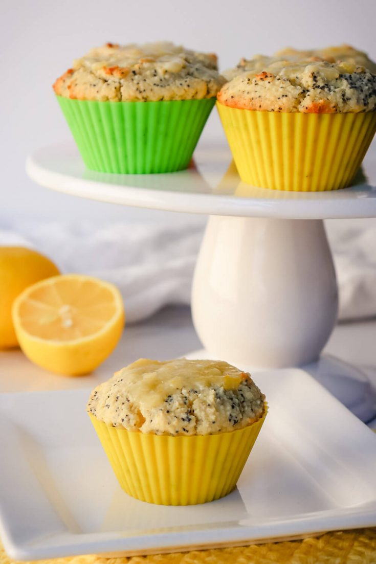 Keto lemon poppy seed muffins on a pedestal and plate
