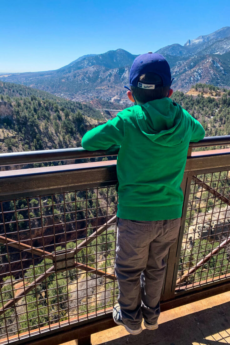 Boy looking out over a mountain view from Cave of the Wonds
