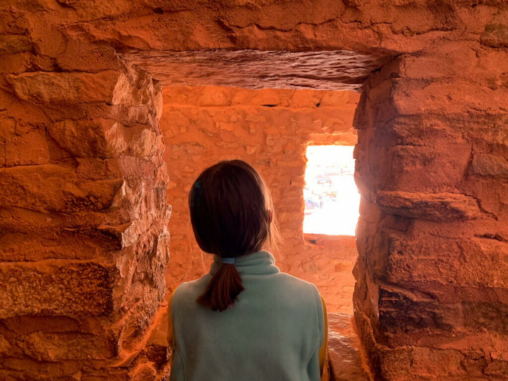 Girl looking out a window at the Manitou Cliff Dwellings