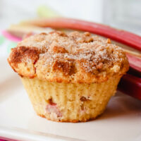 Front view of a keto rhubarb muffin with rhubarb in background