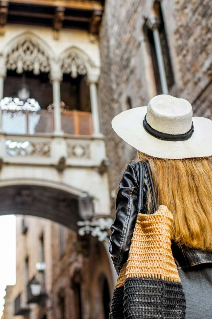 A woman in a white hat looking up at the Spanish bridge of sighs