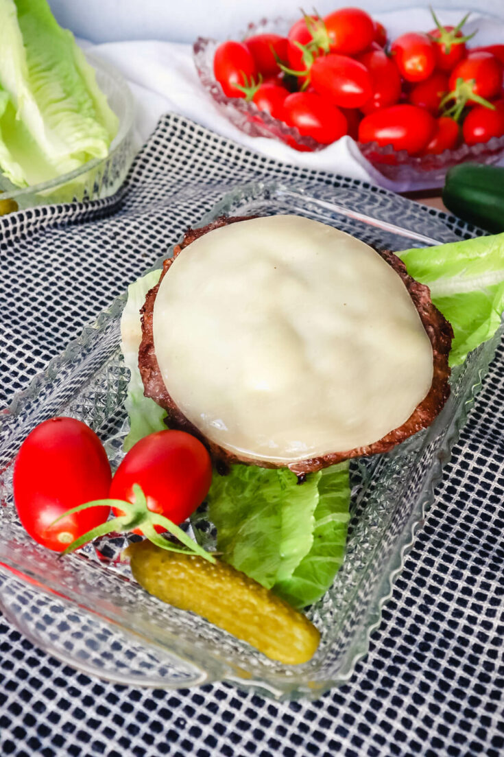 Burger on a plate with lettuce and tomatoes, pickles